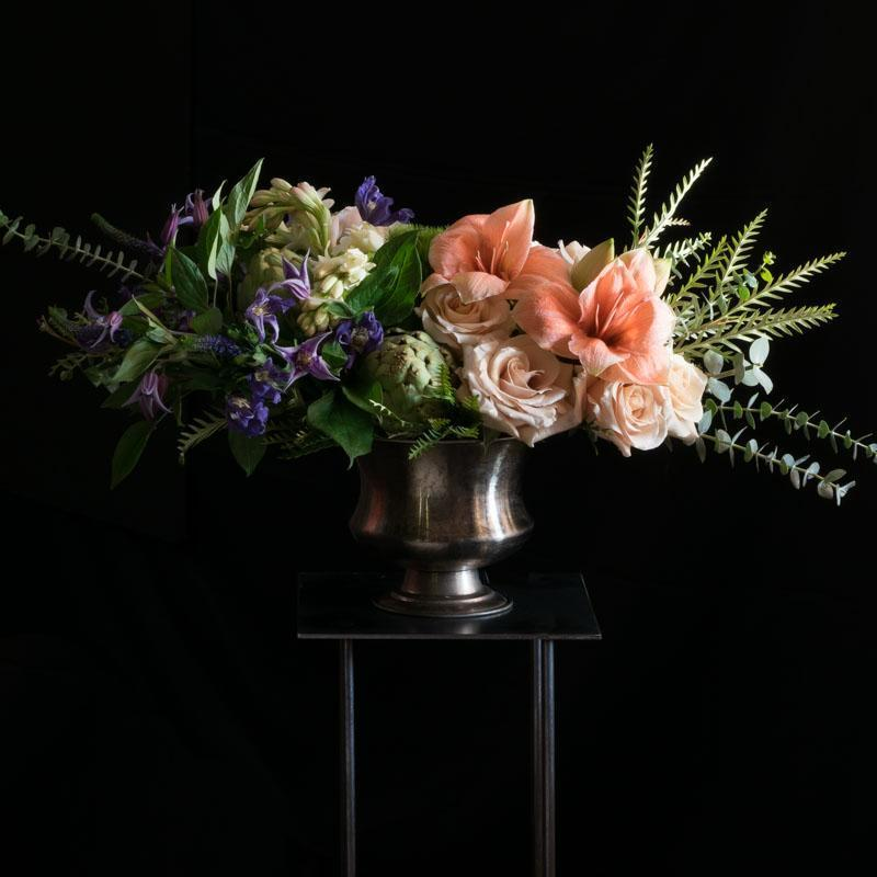 Floral design with light orange amaryllis and roses.