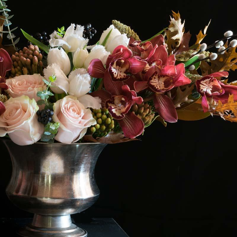 Boutique flower arrangement of burgundy orchids, white tulips, and roses