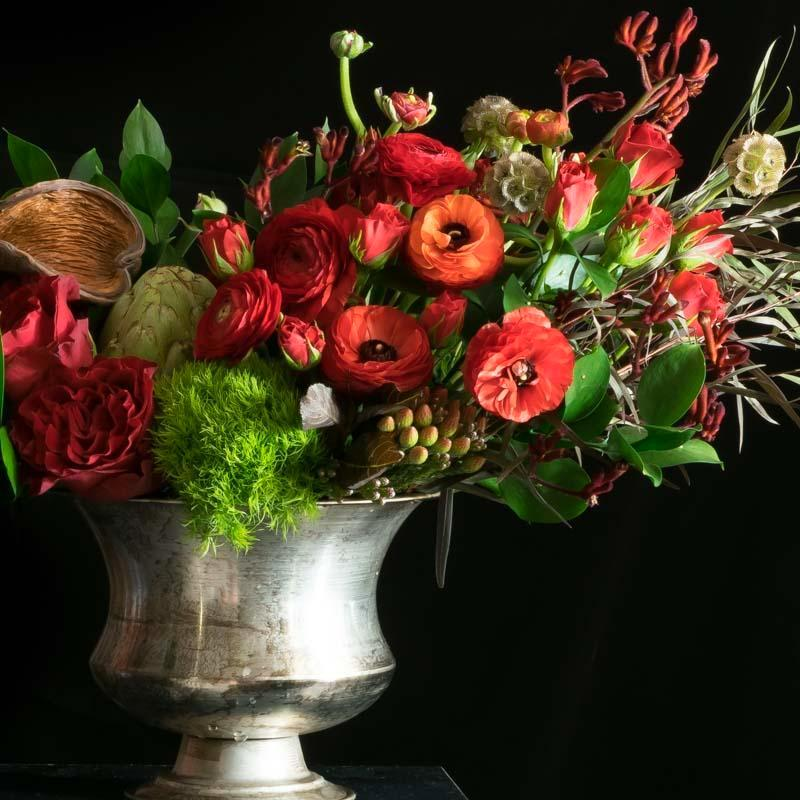 Large floral arrangement of red flowers including red roses, red tulips, and red anemones