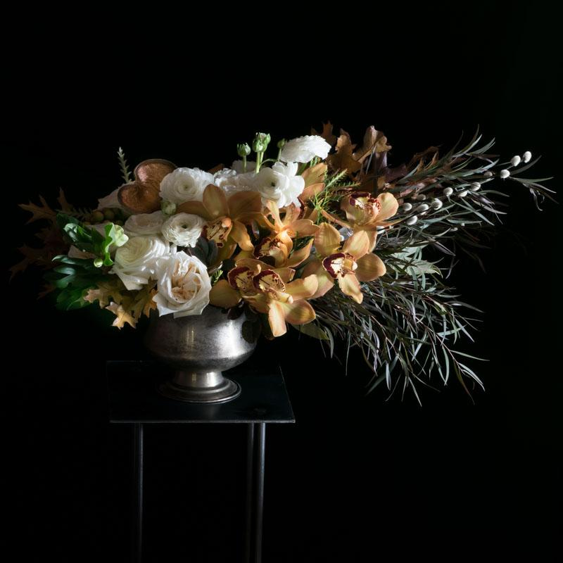 Large floral design with brown orchids and white ranunculus and roses