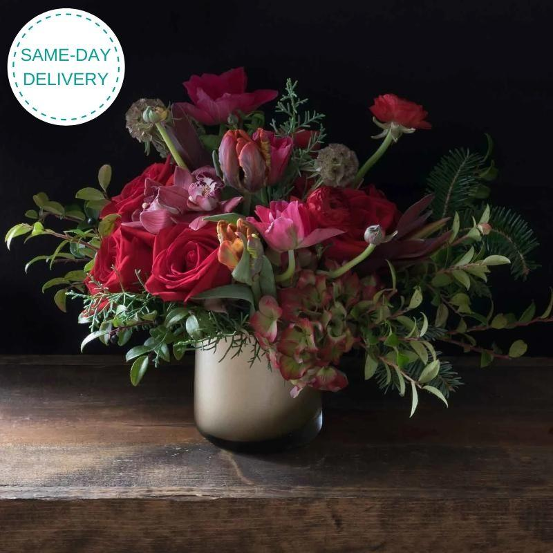 Boutique holiday flower arrangement with red roses, tulips and hydrangeas.