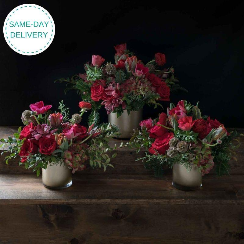 Set of 3 holiday, Christmas flower arrangement with red roses, red anemones, red ranunculus and tulips.