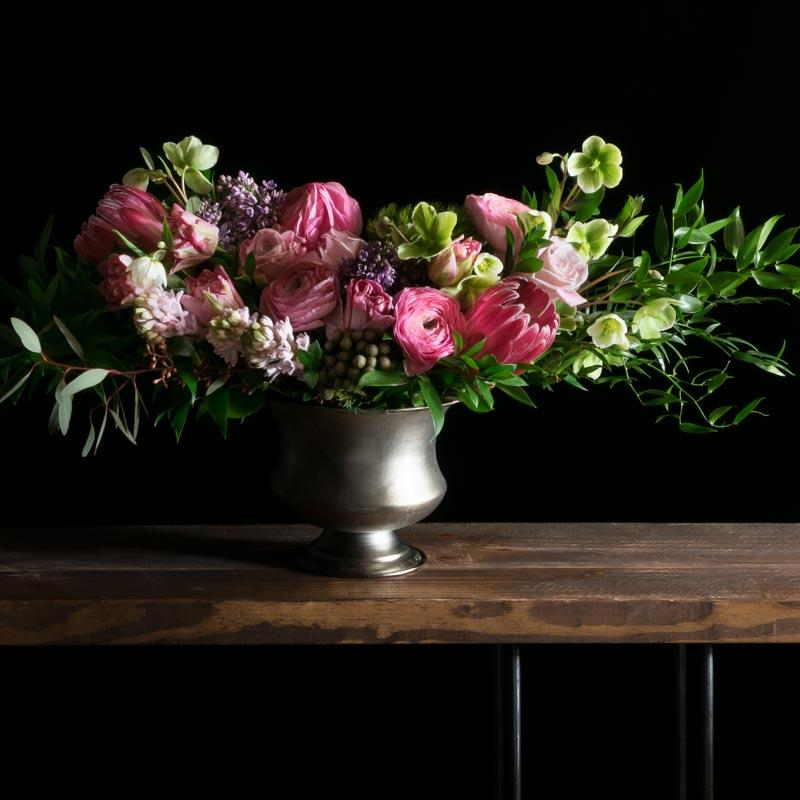 Beautiful boutique flower arrangement with pink ranunculus, pink roses, and protea