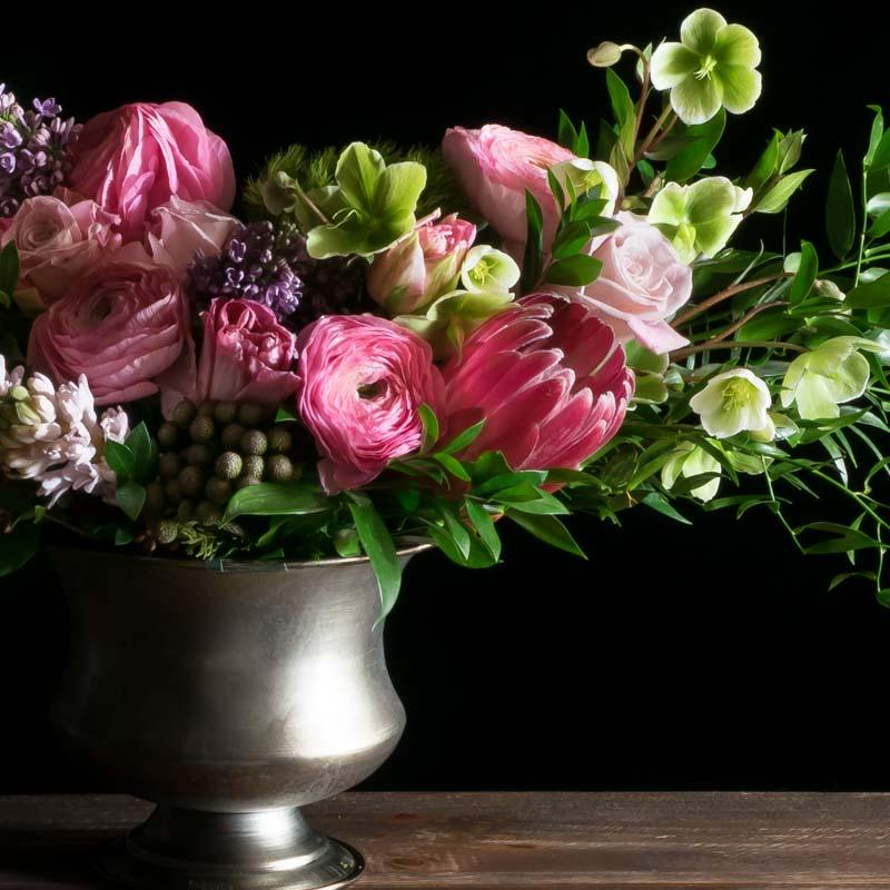 Beautiful luxe boutique flower arrangement with pink ranunculus, pink roses, and protea