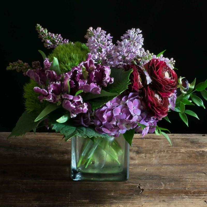 Floral arrangement of purple, lavender flowers, hydrangeas, parrot tulips, lilacs and the gorgeous burgundy ranunculus.