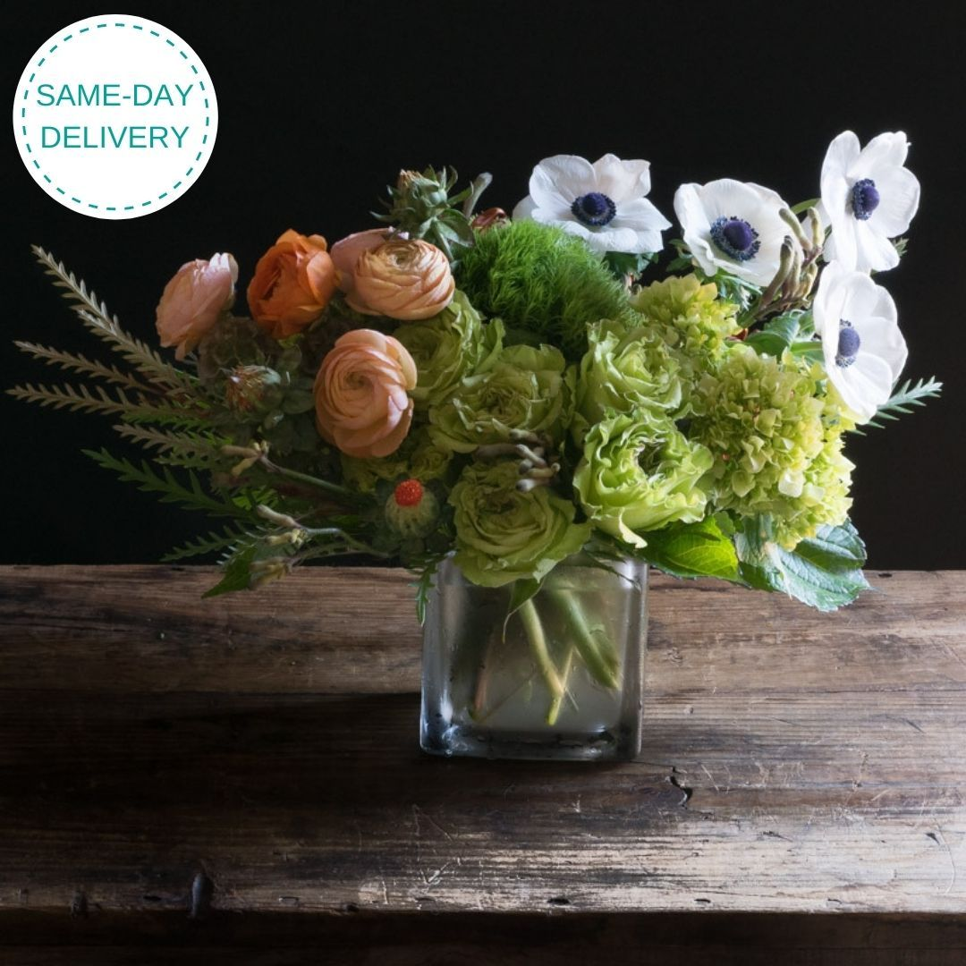 Beautiful boutique fall floral arrangement wth orange roses, light orange ranunculus, green roses, and white anemones.