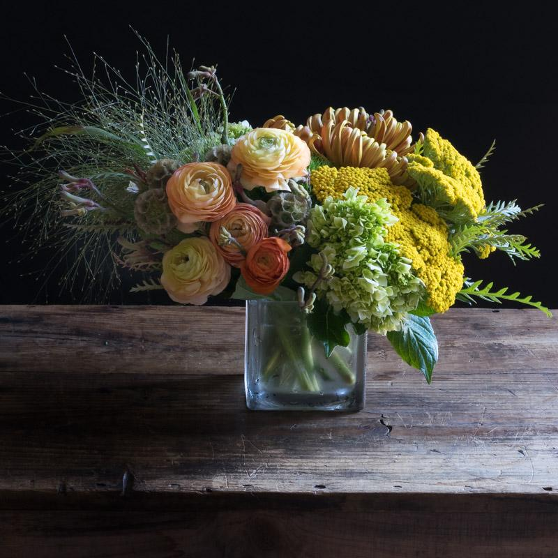 Top luxury colorful fall flower arrangement with light orange ranunculus, yellow flowers.