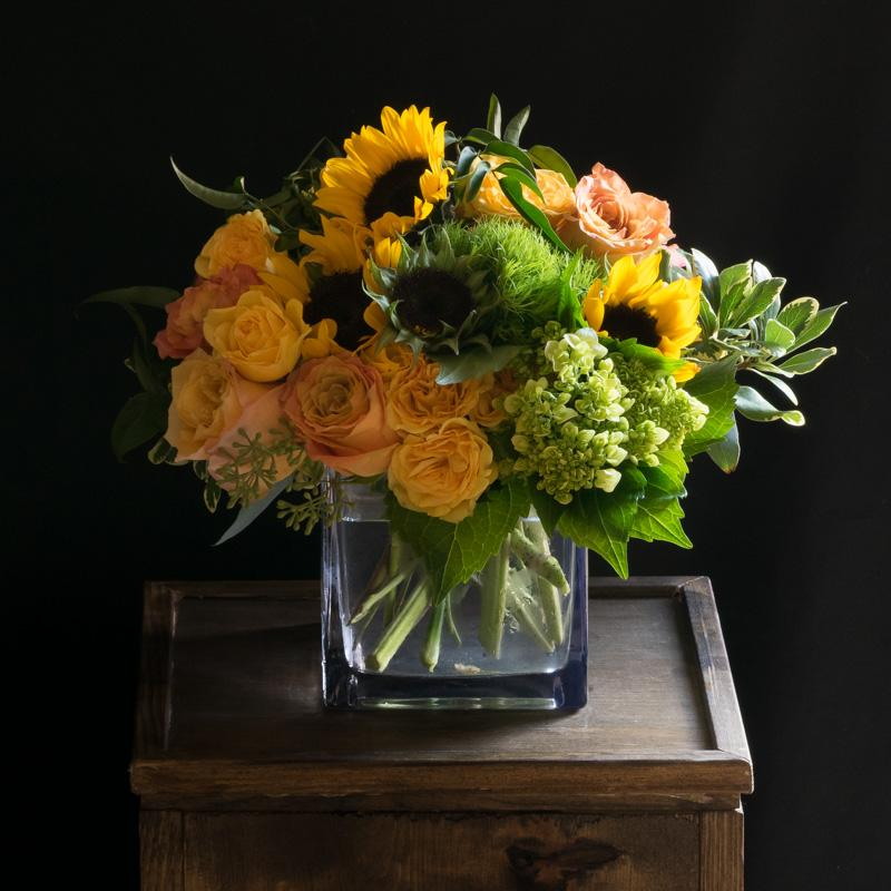 Unique sunflower floral arrangement with yellow and orange roses, and green mini hydrangeas.