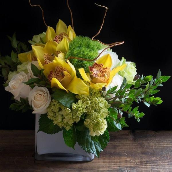 Top unique luxury floral arrangement with yellow orchids, white roses, and mini green hydrangeas.