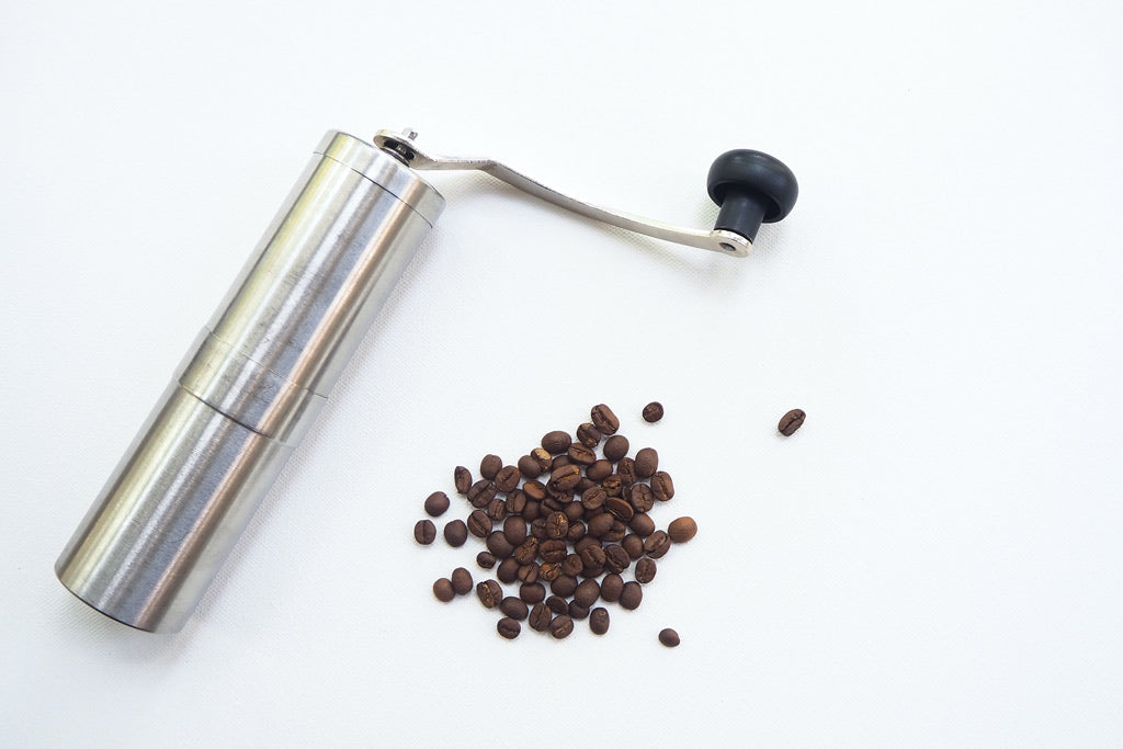 Brown coffee beans near gray stainless steel