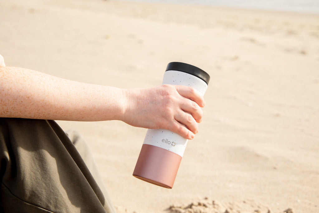 Person holding white and black coffee mug