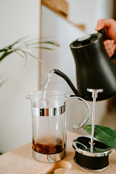 Faceless person pouring hot water into french press