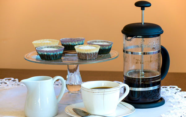 French press beside footed rack cupcake