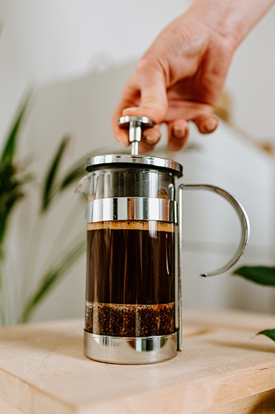Person pressing plunger of coffee maker
