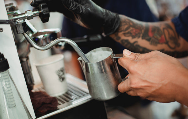 barista frothing milk with steam wand