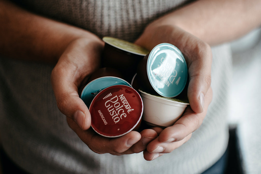 Person holding coffee pods