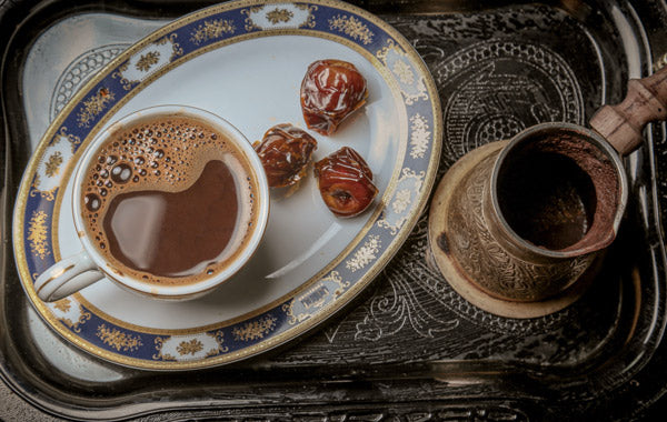 cup of coffee with dates on serving tray