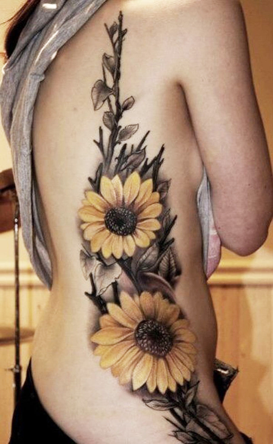 Realistic Colored Yellow  Sunflower Floral Flower Side Rib Tattoo Ideas for Women at MyBodiArt.com