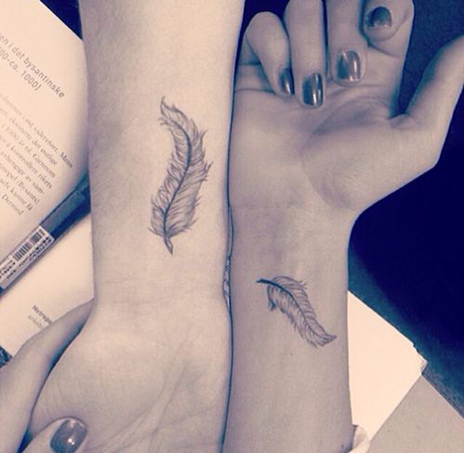 Cute Small Plume Feather Matching Couple Best Friends Wrist Tattoo Ideas for Women at MyBodiArt.com