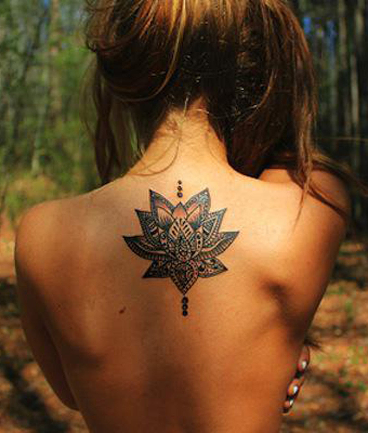 Tribal Lotus Upper Back Tattoo Ideas for Women at MyBodiArt.com