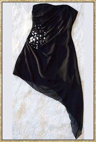 Black strapless dress with rhinestone embellishments along right side and a material drape design on the left side