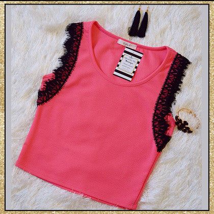 Pink sleeveless crop top with black lace detail around arm holes