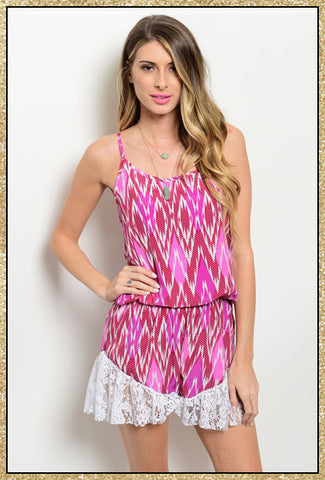 Spaghetti strap light pink, dark pink and white romper with diamond shaped print and white lace detail along trimming of the shorts