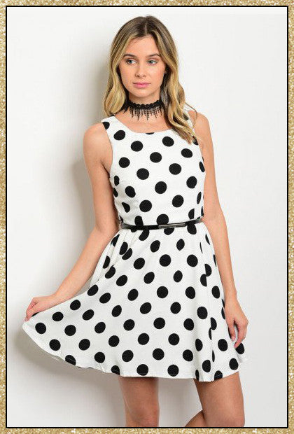 White sleeveless dress with large black polka dots and skinny black attached belt
