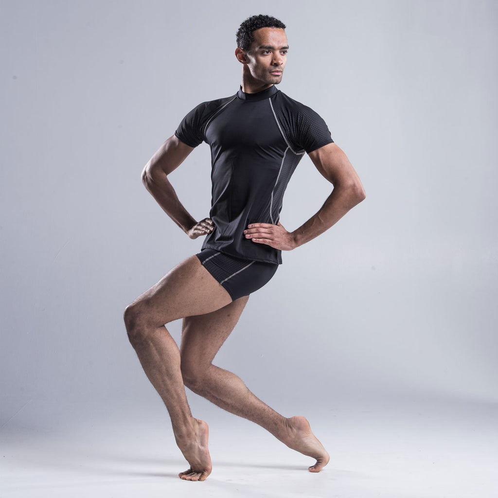 Brandon Lawrence wearing a black fitted turtleneck with a drop sleeve and shaped body allowing freedom of movement. A shaped perforated section down each side provide air flow throughout the top.  A contrast stitch along the drop sleeve  ties in with shorts and legging in the collection.