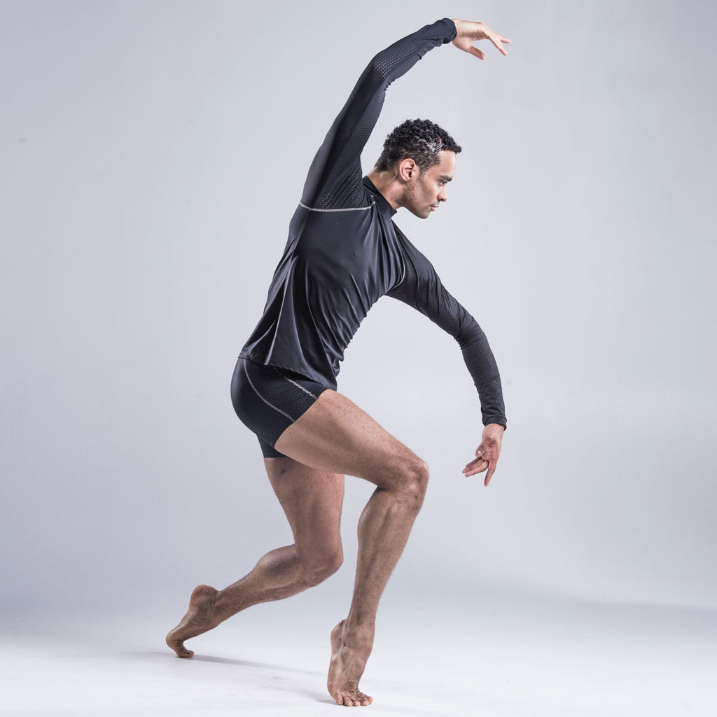 Brandon Lawrence wearing black dancer shorts with no uncomfortable front seam and the wide waste band holds the leggings securely in place.  The perforated side section has a layer of contrast fabric running underneath designed to match the outside feature stitching
