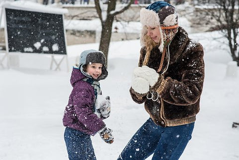 family playing snow winter hats