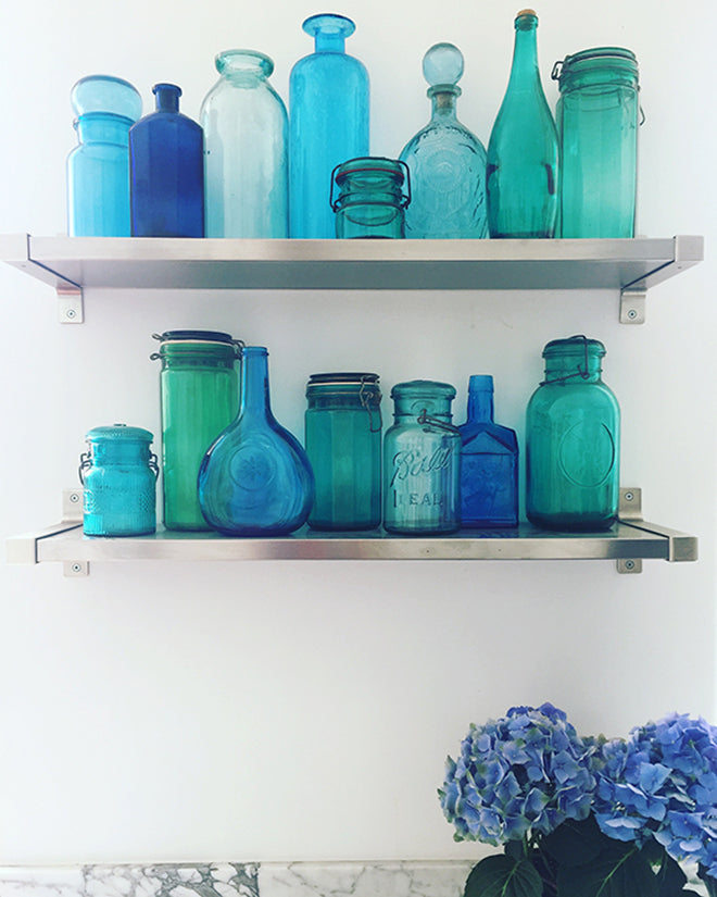 Shelves Displaying Collection of Antique Blue Bottles