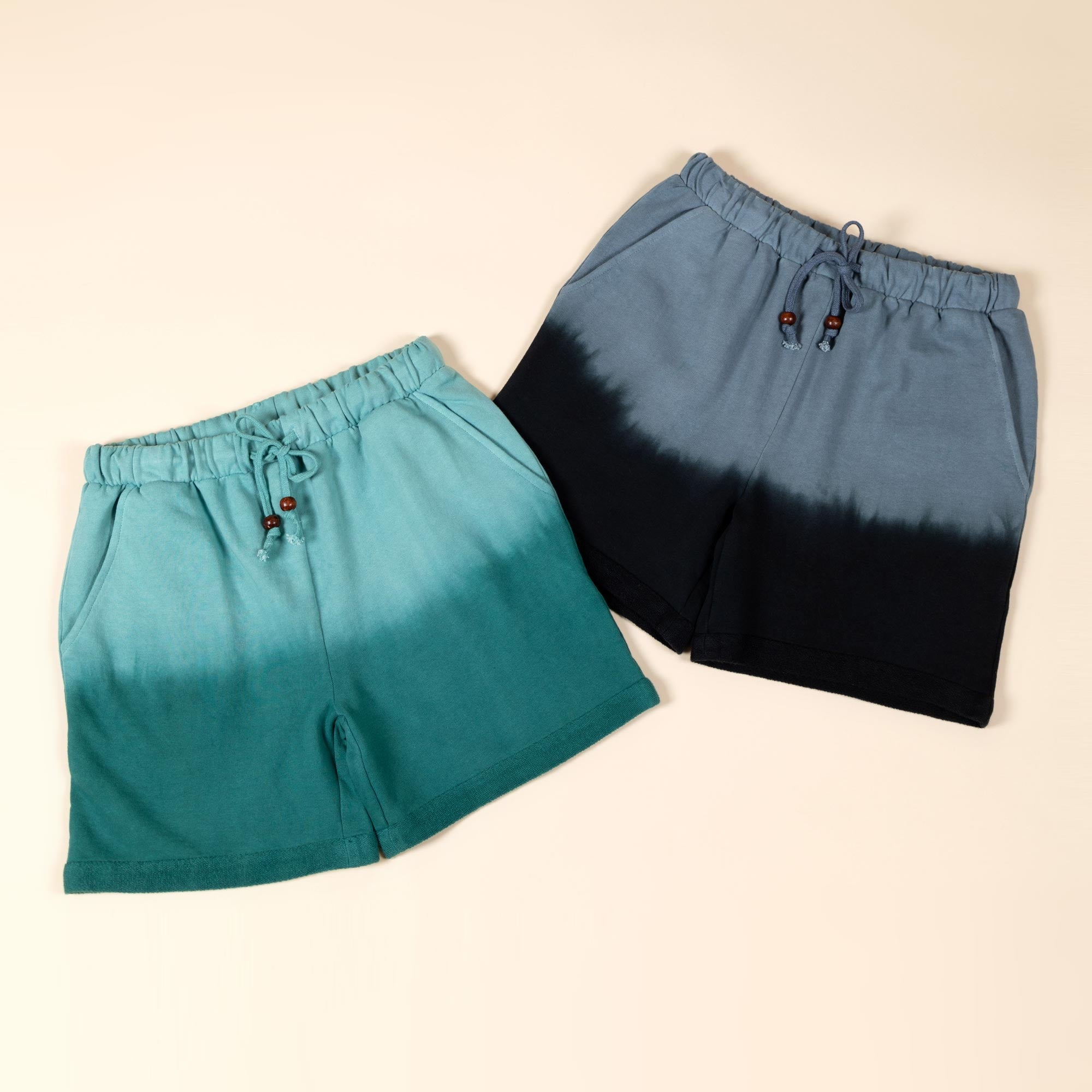 Three pairs of ombre dyed shorts lay on a clean background