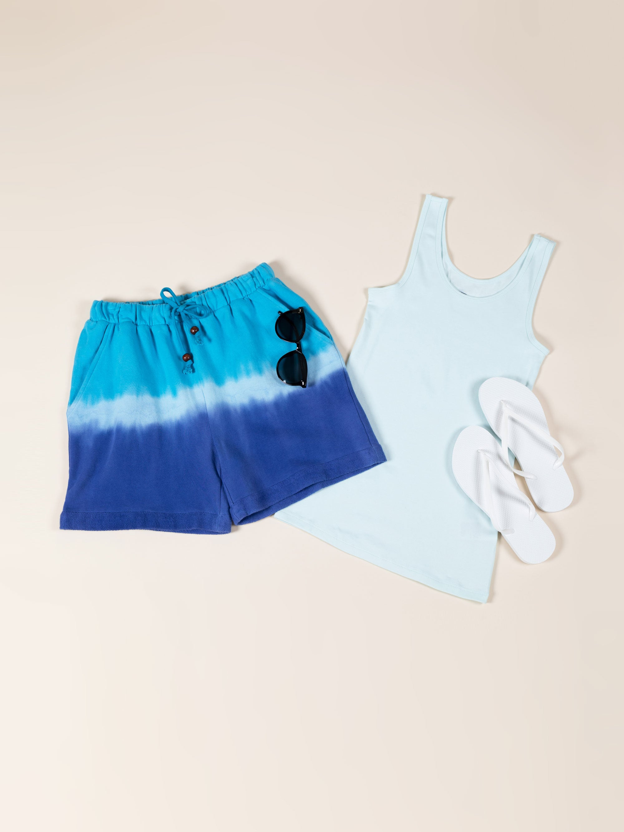 A pair of hand-dyed shorts are positioned to the left of a brightly-colored tank top and white flip-flops