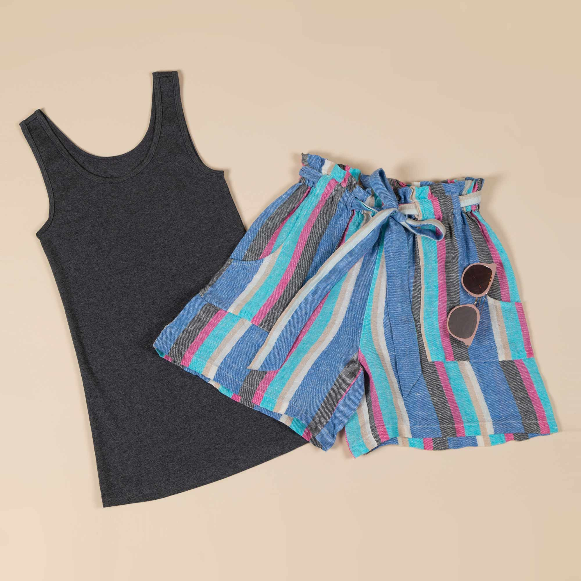Artisan crafted shorts — with sunglasses hung on the pocket — lay atop a solid colored tank top.
