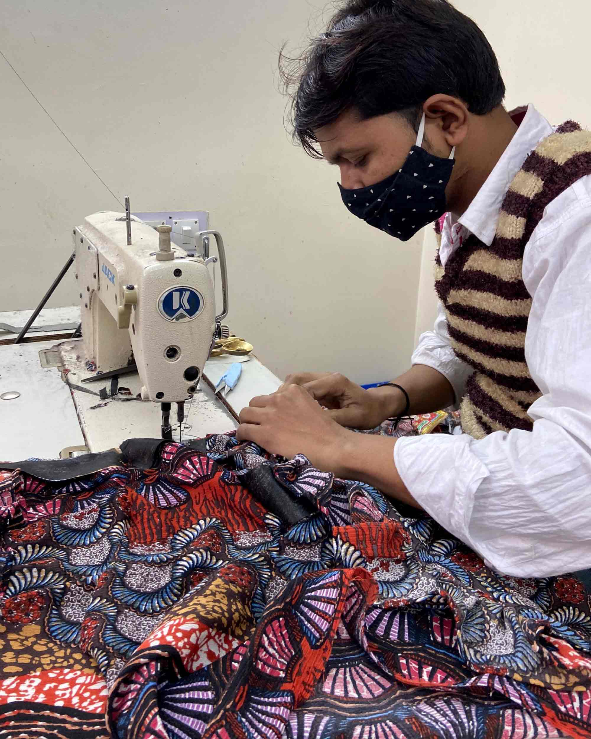 An artisan carefully sowing a dress using whimsical fabric