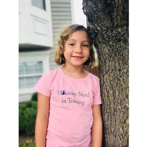 "Girl wearing ""History Nerd in Training"" Youth shirt for girls - Light pink from The History List"