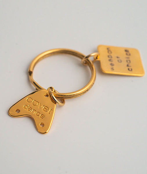 Back of gold-plated tap charm with Covet Dance logo