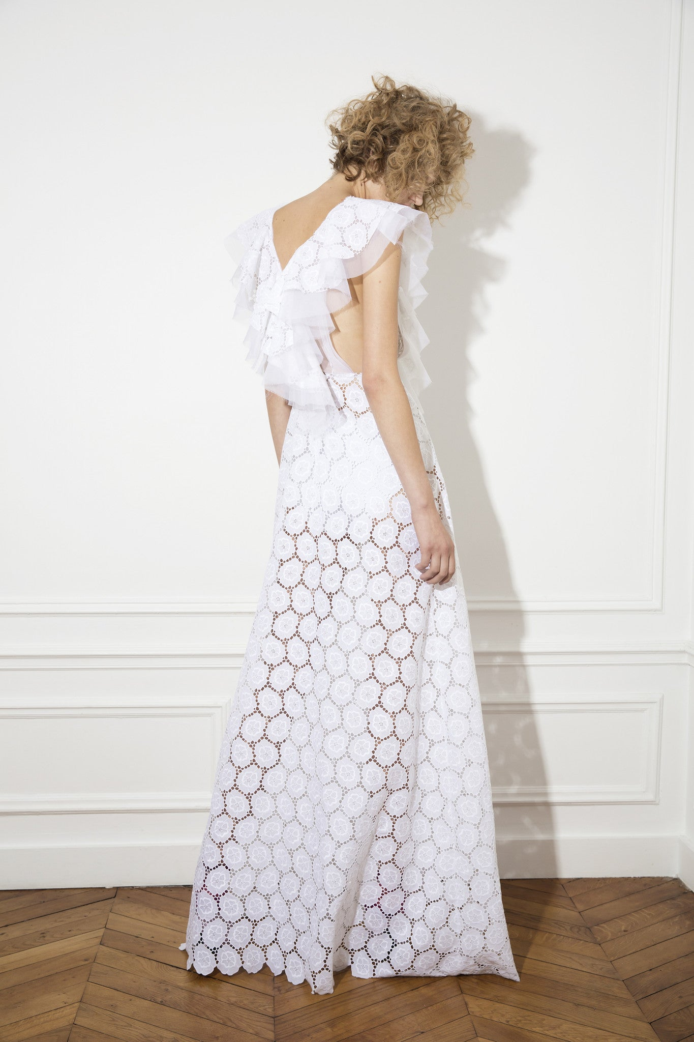 a long, white sleeveless gown with a v-shaped frill