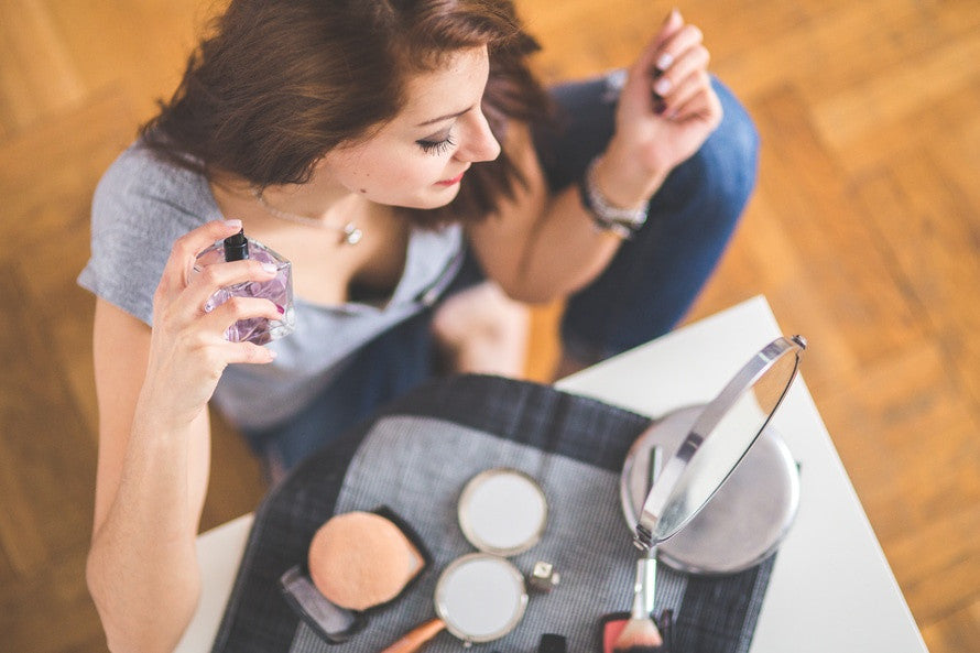 Woman sitting  with makeup, applying perfume while looking in the mirror. Mia's aromatherapy roll-ons and perfume, nature in a bottle. Photo courtesy of Pexels.