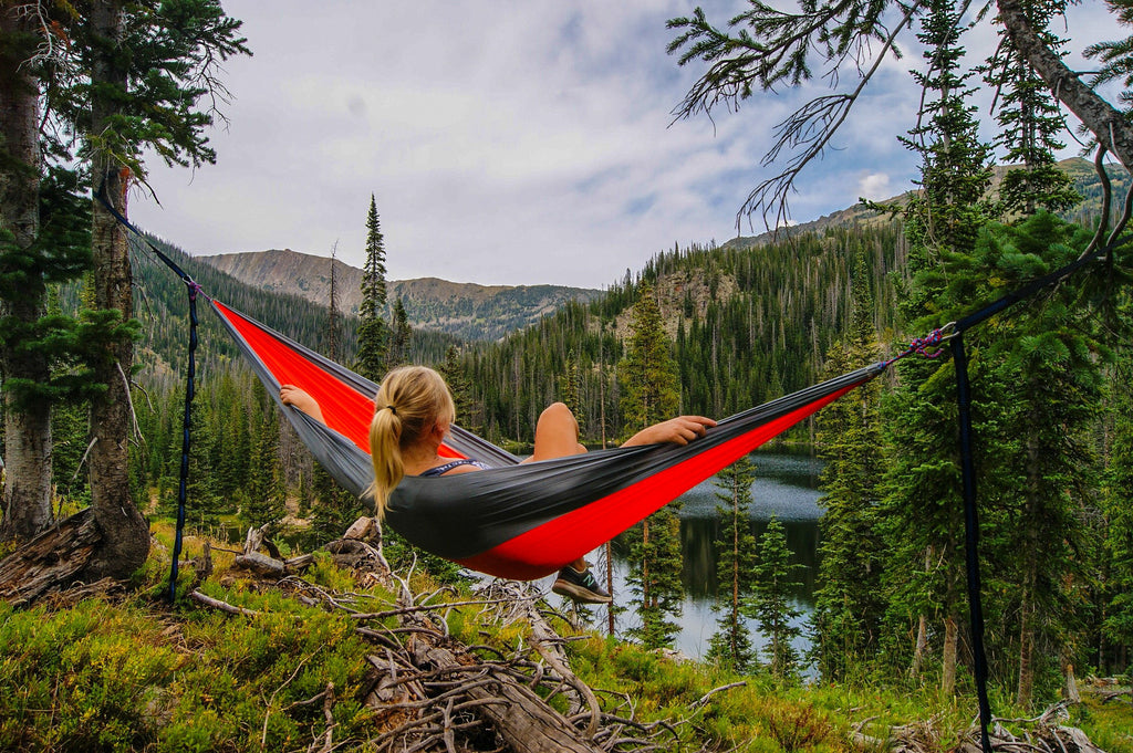 Woman sitting in hammock overlooking the wilderness. Mia's Aromatherapy Support, nature's therapy formulated just for you. Photo courtesy of UnSplash.