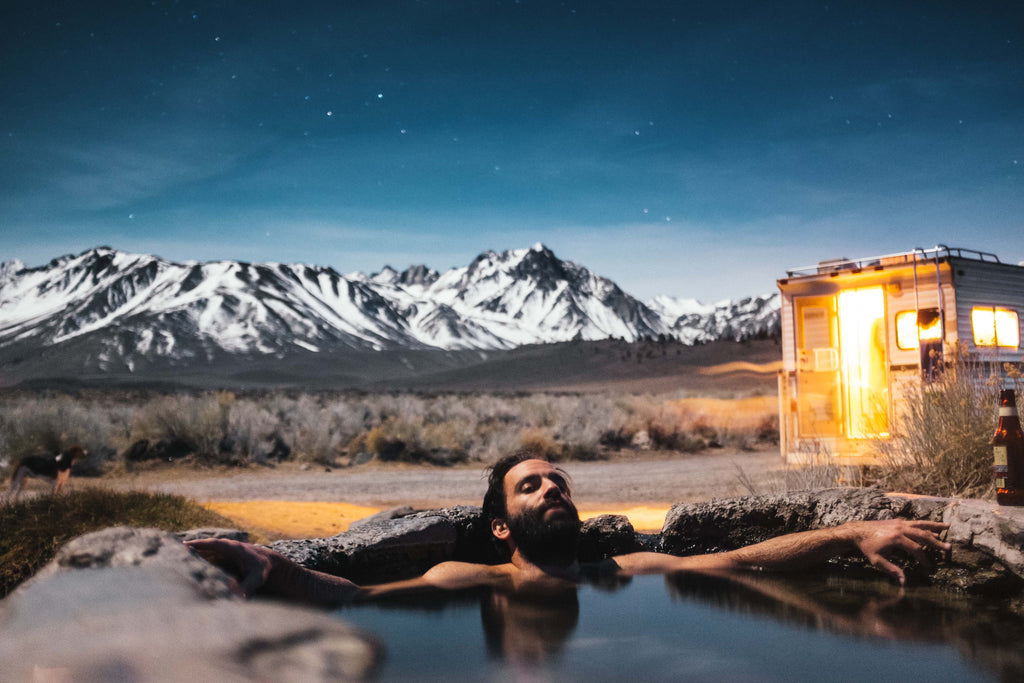 Man enjoying hot springs in the wilderness. Personal care aromatherapy products for men is nature in a bottle. Photo courtesy of UnSplash.