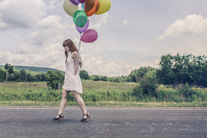Woman walking down street in the country with balloon's in her hand. Give the gift of nature with Mia's Aromatherapy. Photo courtesy of Pexels.