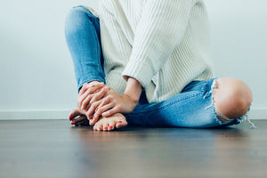 Woman sitting on the floor with hand on her feet. Restore and protect using Mia's aromatherapy products. Photo courtesy of StockSnap.