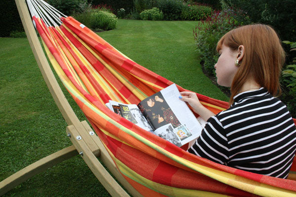 Woman reading magazine in hammock in garden