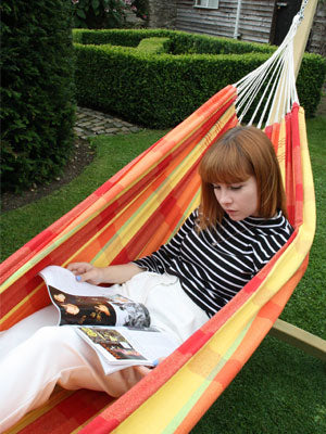 Woman lying on back in hammock reading magazine