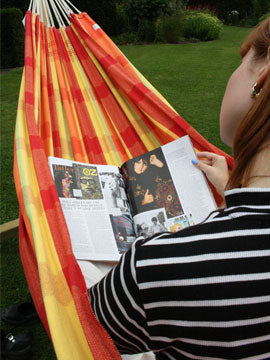 Woman in hammock reading magazine