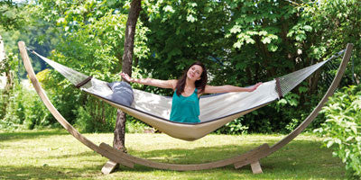 Woman sat on hammock supported by wooden hammock stand