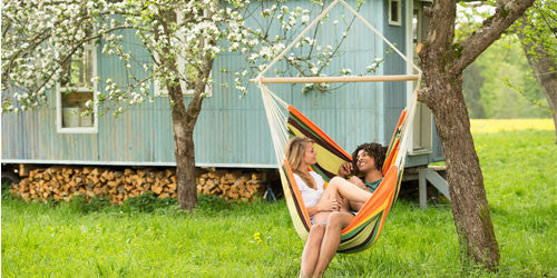 Man and woman sat in hanging hammock chair