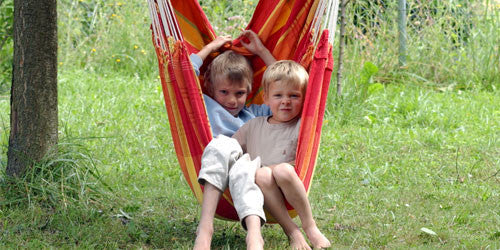 Two children sat in hanging hammock chair